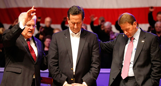 Santorum recibe la dendición del pastor Dennis Terry en un acto en Louisiana.
