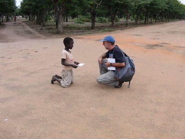 Ricardo Olmedo, redactor del programa, hablando con un niño en las afueras de Inhaminga, Mozambique.