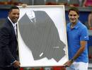 Federer of Switzerland and Will Smith pose with a suit Smith wore in the movie