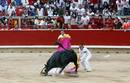 A runner gets knocked down by a Torrehandilla fighting bull at the bullring during the final running of the bulls at the San Fermin festival in Pamplona