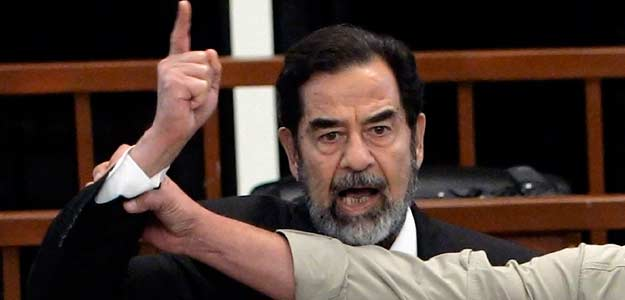 Former Iraqi President Saddam Hussein yells in court as he receives verdict, as bailiff attempts to silence him, during trial in Baghdad