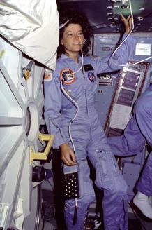 Sally Ride de pie junto a la compuerta del transbordador Challenger con el que viajó en dos ocasiones al espacio