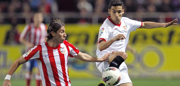 El delantero del Sevilla CF, Jesús Navas (d), lucha el balón con el brasileño Filipe Luis