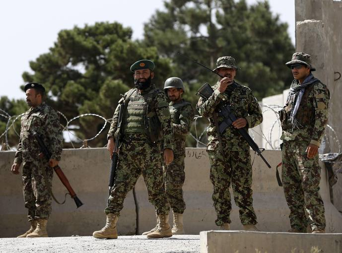 Soldados afganos vigilan la entrada a una base de la OTAN atacada