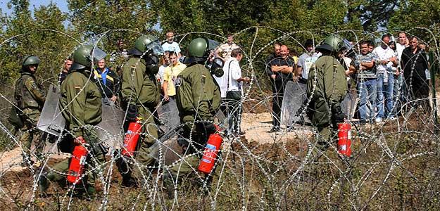 Soldados alemanaes de la fuerza de la OTAN en Kosovo llegan con extintores al paso fronterizo de Jarinje ante la mirada de un grupo de serbios.