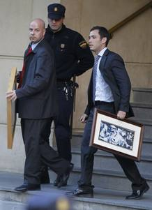 Spanish judge Baltasar Garzon's assistants carry two pictures belonging to him outside the Spain's High Court in Madrid