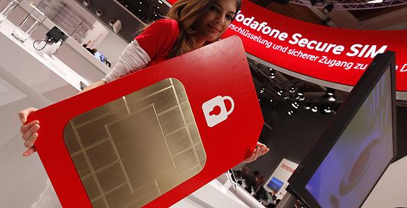 Una azafata posa con una tarjeta SIM gigante en el stand de Vodafone durante la feria CeBit celebrada en Hanover el pasado mes de marzo.