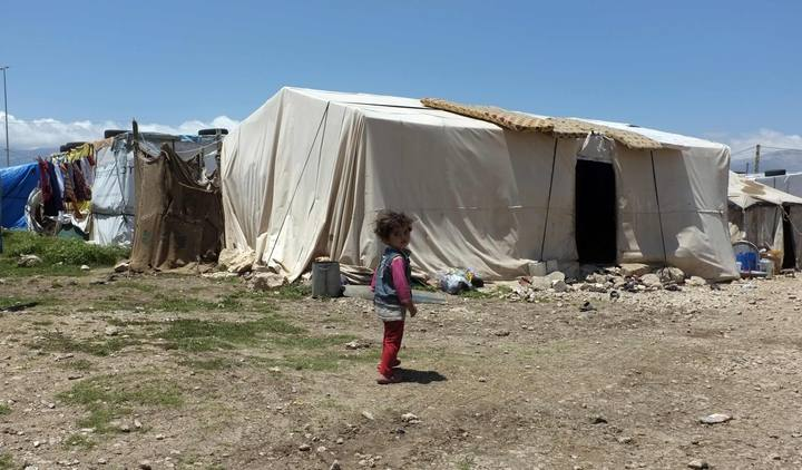 A Syrian girl stands in a refugee camp in the east Lebanese town of Anjar near the Syrian border