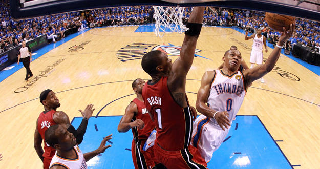 Russell Westbrook, de los Thunder, intenta encestar ante la oposici&oacute;n de Chris Bosh, de los Miami Heat.