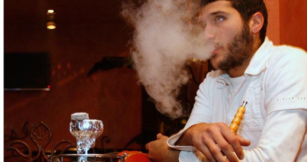 Un hombre fuma 'shisha' en un bar de París.