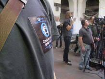 Uno de los asistentes a la rueda de prensa del 15m luce una pegatina con la convocatoria del sábado