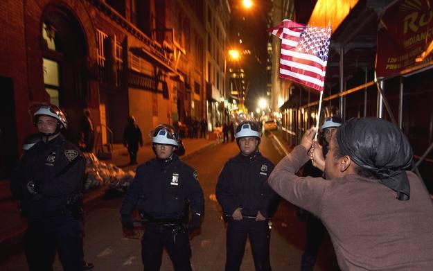 Uno de los miembros de Occupy Wall Street ondea una bandera ante el cordón policial