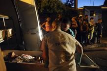 Unos trabajadores retiran el cadáver de una persona fallecida por disparos de bala en Salvador de Bahia