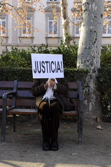 """Una mujer de las varias decenas que se han concentrado frente al Supremo para apoyar a Garzón, con un cartel de """"Justicia"""" sentada en uno de los bancos."""