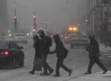 Varias personas desafían al temporal de frío y nieve en Chicago y cruzan una calle.