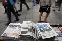 Varios ciudadanos caminan al lado de un kiosko en el que todos los periódicos abren con el anuncio de ETA.