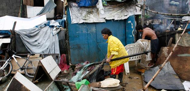 Vecinos limpian sus chabolas tras el paso del tifón Nesat en Marikina, Filipinas