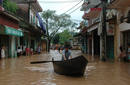 A resident pushes a boat along flooded road in Vietnam's northern Bac Giang province