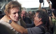 Francesc Osan, director de la ONG Acció Solidaria, golpe cariñosamente a Roque Pascual, tras su llegada al aeropuerto de El Prat.