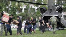 Voluntarios transportan provisiones a un helicóptero militar que vuela a los pueblos afectados a dejarles víveres y recoger a los supervivientes