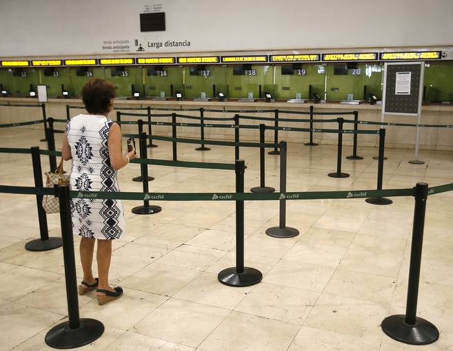 A woman looks at empty ticket booths in Sants railway station during a nationwide strike by rail workers in Barcelona