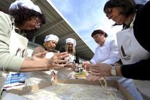 Varias mujeres que han perdido sus casas preparan pasta para la comida del Domingo de Pascua en el campo de Acquasanta.