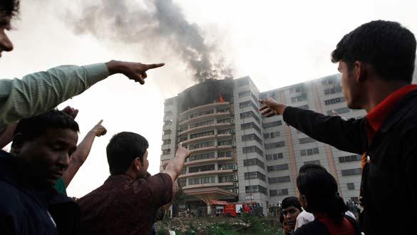 Trabajadores señalan a un hombre en la ventana de la fábrica en llamas.