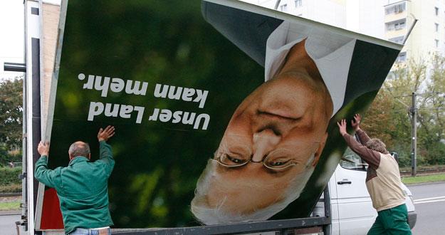 Trabajadores retiran un cartel de campaña del candidato del SPD.