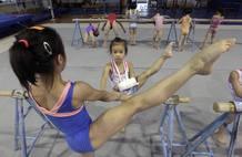 Joven gimnasta que se rompió el brazo durante un entrenamiento, practica junto a sus compañeras en un centro deportivo de Wuhan, China.